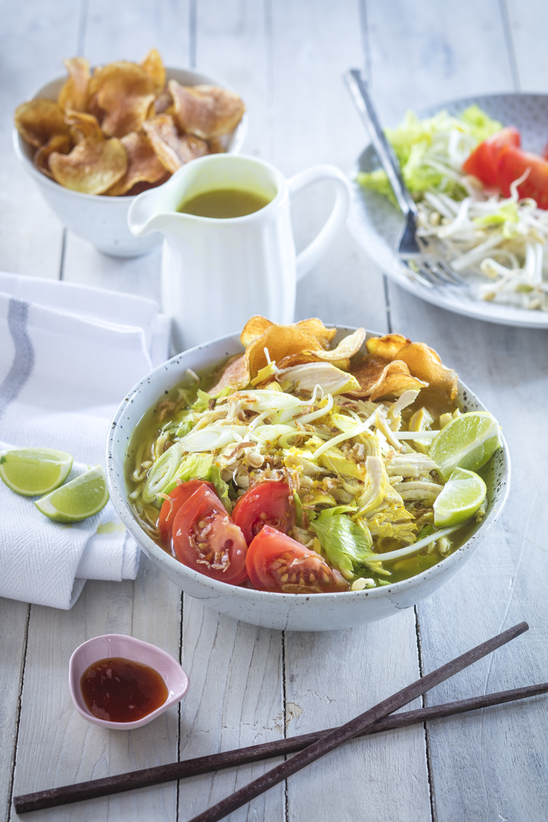 A bowl full of tomato, beansproyts, lime, potato chips and Indonesian broth